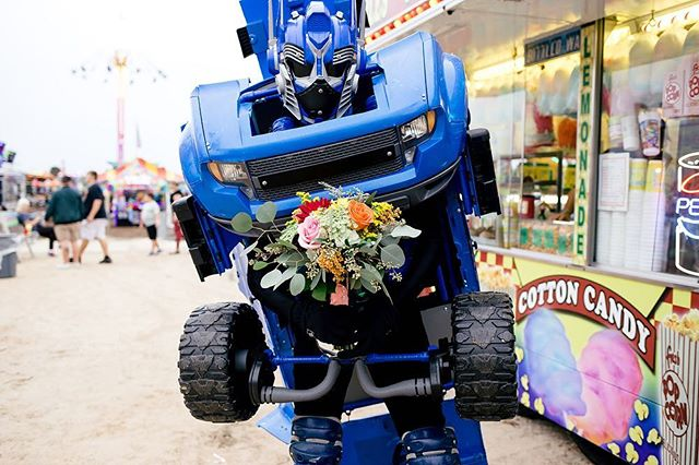 A transformer holding a bouquet in the middle of an elopement at the county fair. ✅⠀ ✨⠀ SWIPE to see the babes!⠀ •⠀ •⠀ @pattibuds  @meaganjoansalon