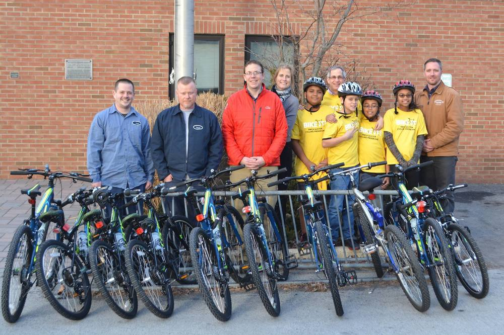 From left, Central Hudson employees Kris Mead, Vincent Boughton, and Eric Kiszkiel,  YMCA President and CEO Heidi Kirschner and Bicycle Educator Tom Polk, enthusiastic youths and (far right) Central Hudson employee Michael Dooley present and accept 9bicycles for the YMCA of Kingston and Ulster County to benefit the agency's Bike-It! program.