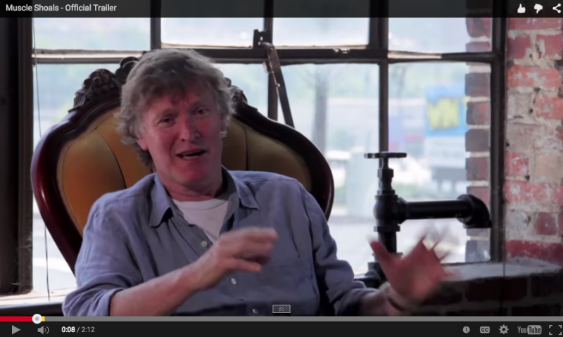 "A still frame from the ""Muscle Shoals"" documentary trailer. Music legend Steve Winwood, interviewed in front of a massive factory loft window, overlooking—what else?—Traffic."