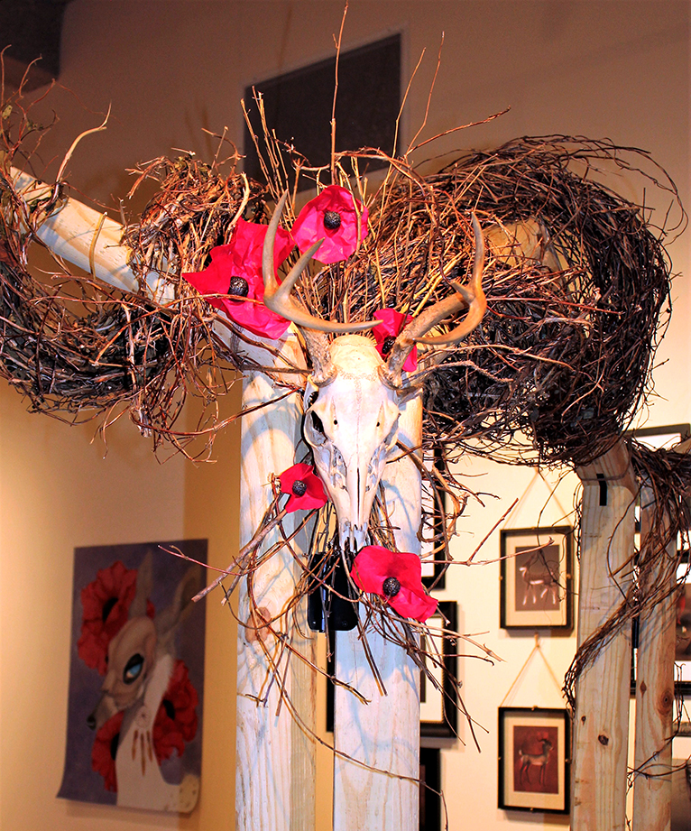 Installation detail of a real whitetail deer skull among grapevine and handmade poppies.