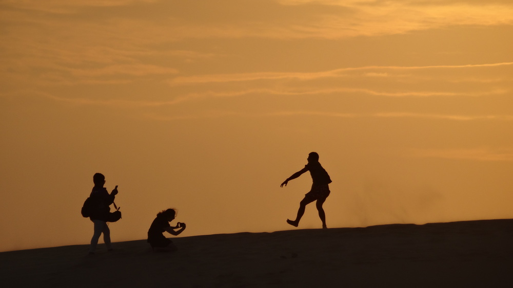 "Tourists trying to get the perfect ""jumping"" shot with the sunset."