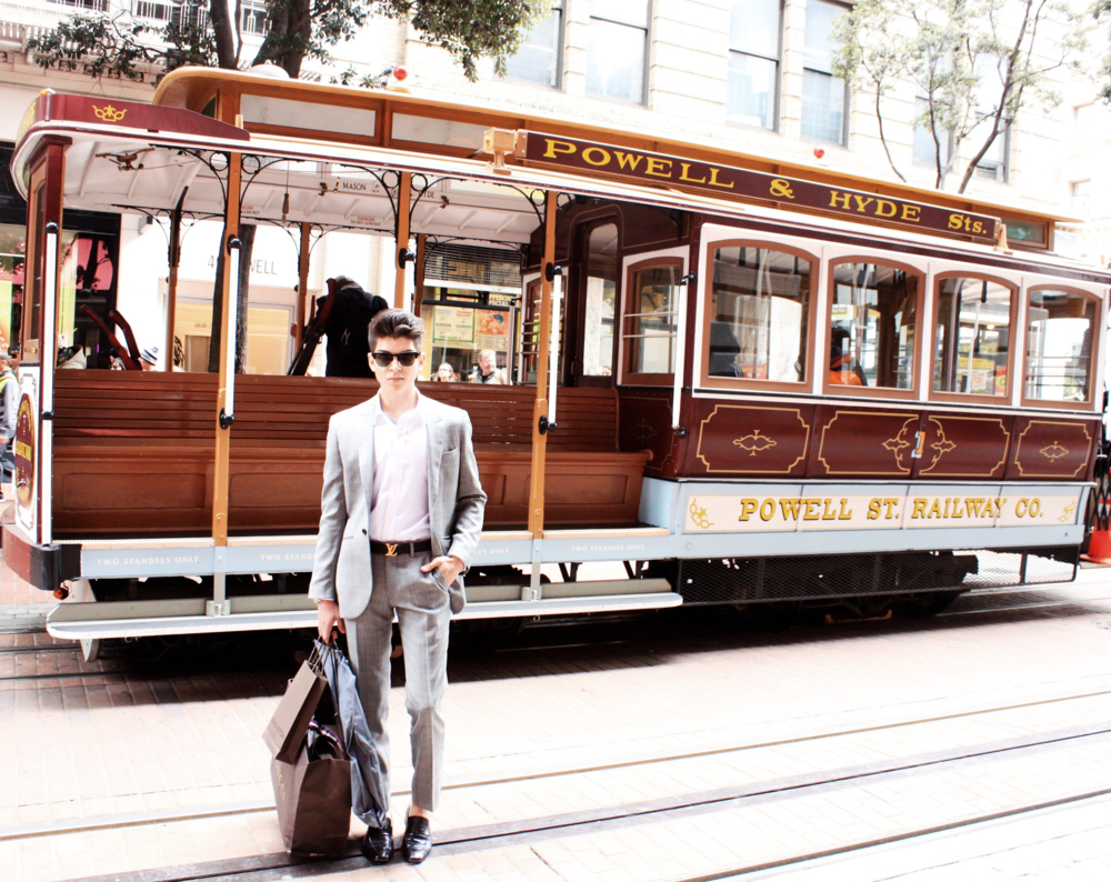 Style blogger Anthony Villegas standing with San Francisco trollies in Union Square.