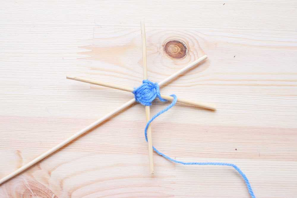 Step 3   With one hand holding the star in place, bring the wool over the top of one of the skewer pieces, wrap it back under and around, then bring it over the top of the next skewer piece, and continue in this way until you start to see the hexagonal weaving begin to form.