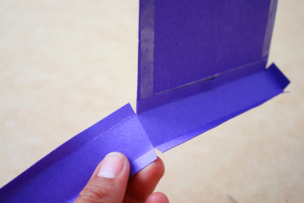 Step 5 Affix double-sided tape around the edges of the bottom box panel. Stick the side panel tabs to the bottom panel. Whenever you get to a corner, make a light score line on the side panel and a cut on each side. This will allow the side panel to fold neatly around each corner.