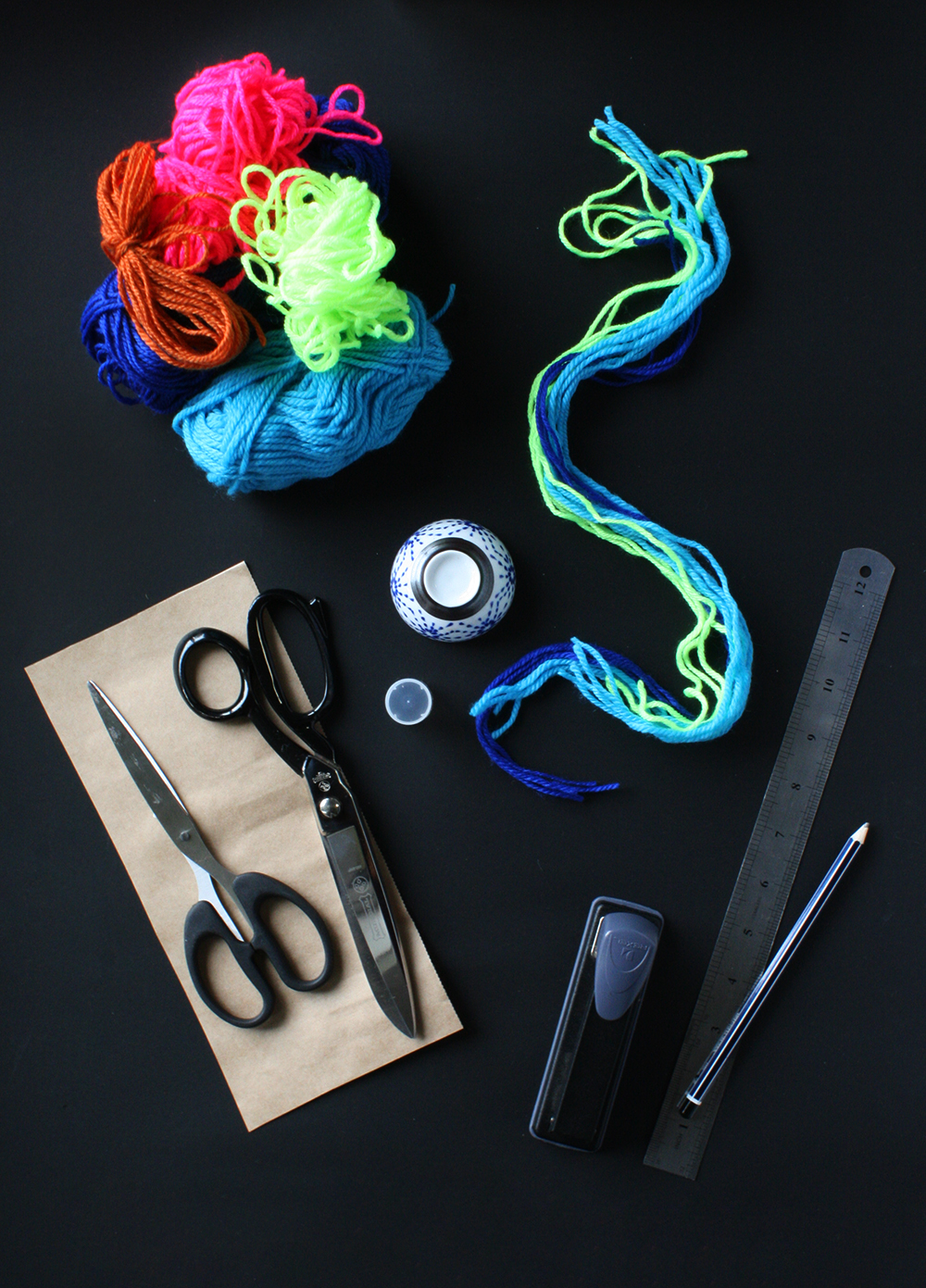 You will need Assorted coloured wool for the pom pom,  16 strands of coloured wool (each 60cm long) Scissors (fabric and paper) Ruler Pencil Plain card stock Stapler Small round bowl Glue stick cap