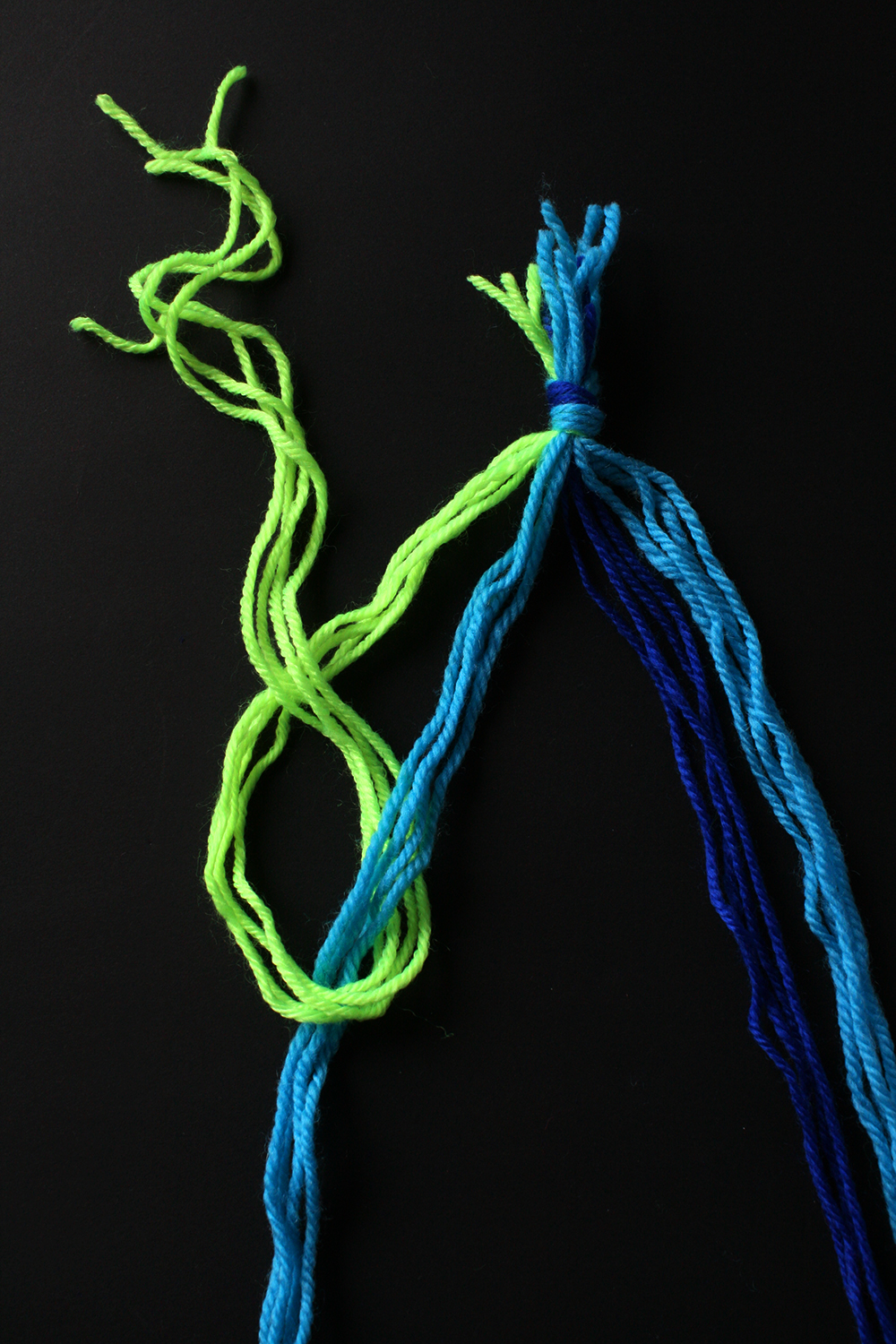 Step 6   This weaving technique is exactly like making a friendship bracelet, except much larger due to the multiple strands of wool. To start the weaving, knot the far left hand bunch of strands (in this case neon yellow) onto the second bunch. Repeat this knot.