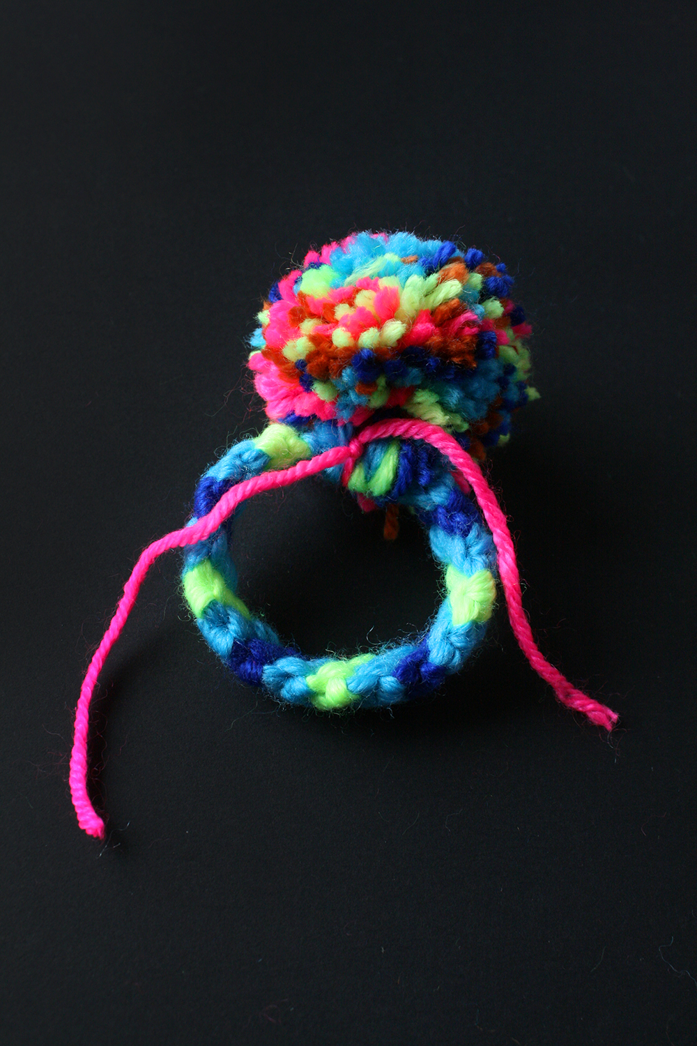 Step 11  Tie the pom pom to the ring in a tight double knot. Make sure the pom pom sits over the knot in the weaving so it hides it and everything is neat. Trim off the excess tie wool, and you're done!