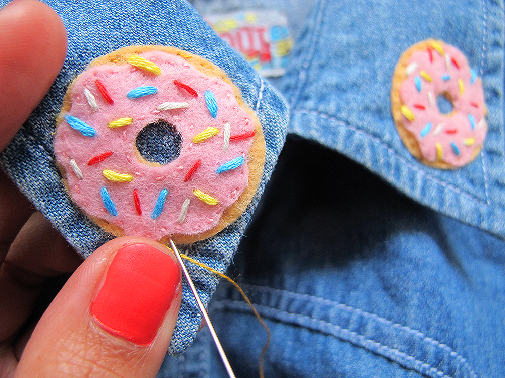 Step 8  Thread a single strand of caramel embroidery thread onto your needle. Using the same simple running stitch, sew a donut onto each collar. Alternatively you could stitch these onto jackets, bags, purses, or anything else that needs a bit of jazzing up!