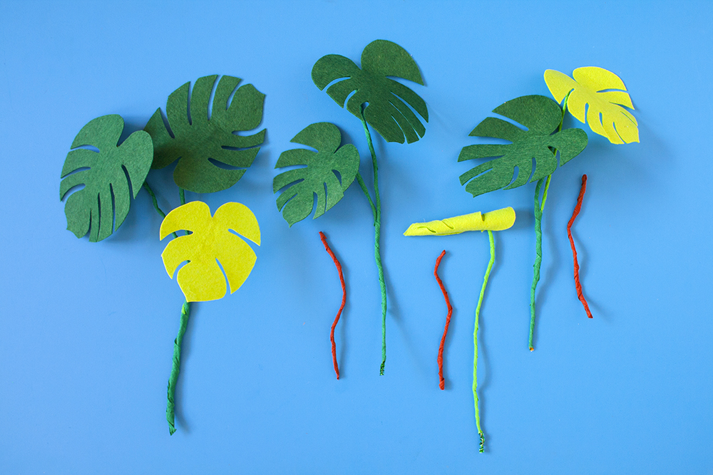 Step 4  Create a variety of different leaf combos by twisting stems together in bunches, then concealing with another layer of crepe paper. You could try rolling up a leaf (for that new leaf vibe) and securing it with blobs of hot glue. You could also create some aerial roots by wrapping shorter lengths of pipe cleaner in brown crepe paper.