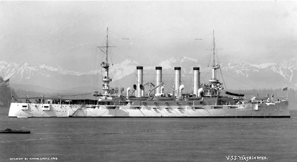 Washington (Armored Cruiser No. 11) at Seattle in 1908, with the Olympic Mountains in the background. Her four tall stacks underscore the emphasis on speed in the design of the armored cruiser, predecessor of the battle cruiser of World War I. (NH 63652)