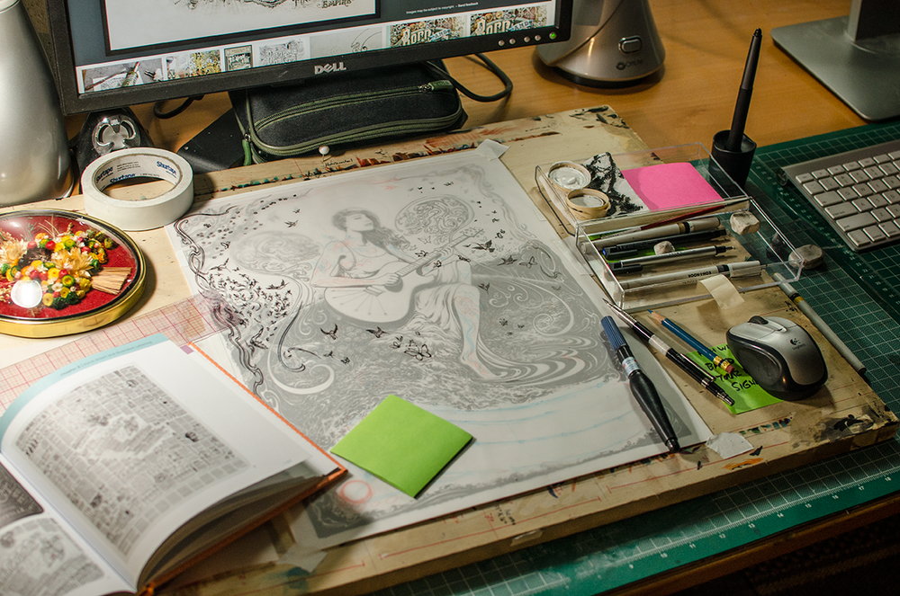 Studio work desk, cluttered with art supplies, computer equipment, various reference books, and a flower talisman. The secondary vellum layer I used to draw extra details and place the text is also visible.