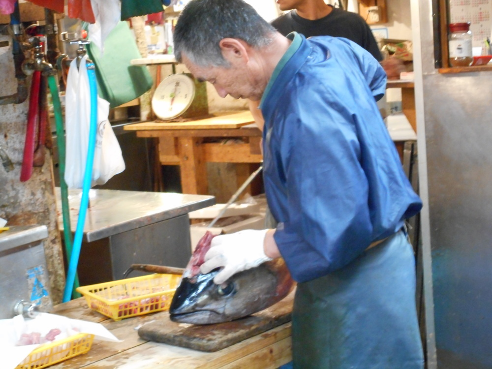 This is a man in the fish market cleaning the meat off an enormous fish head.