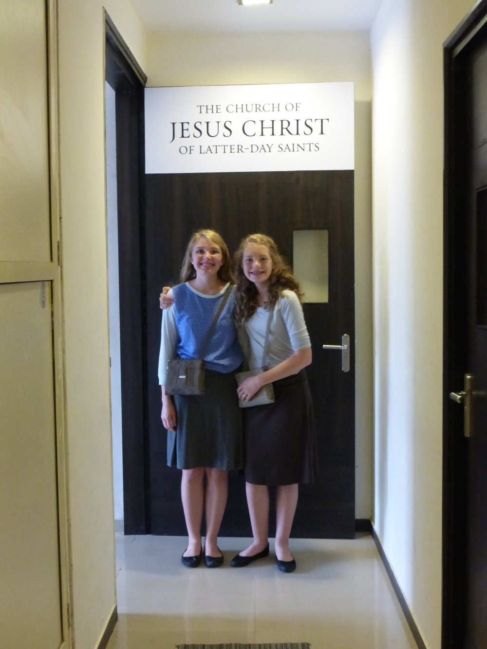 Rebecca & Camilla below the church sign on the door of their area of the building.