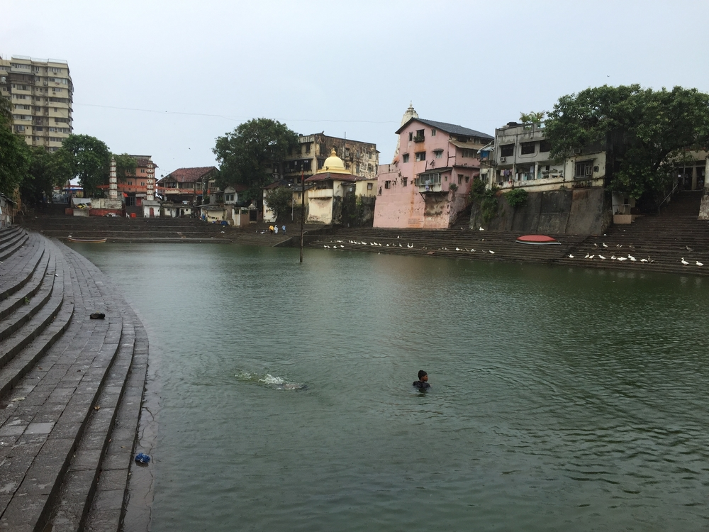 A young boy swimming in a pool that is sacred to the Hindu people.  They believe that someone came and shot an arrow into the ground and water came springing out.