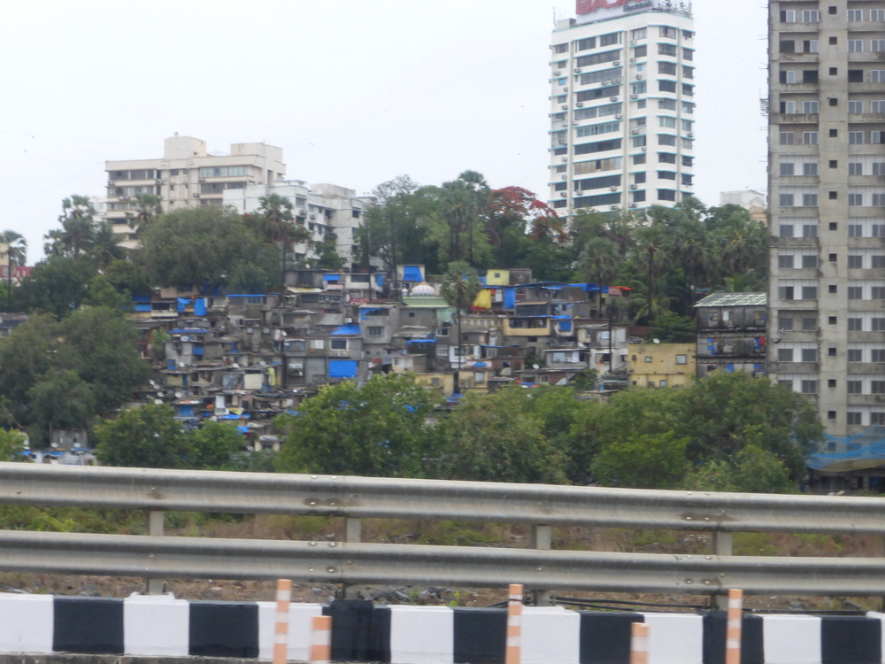 A picture of some of the slums right off the bridge/freeway.  The slums are literally everywhere - in between buildings, shops, roads, etc.  They are like metal boxes built right on top of another.  The bright colors are tarps to keep out the monsoon rains.