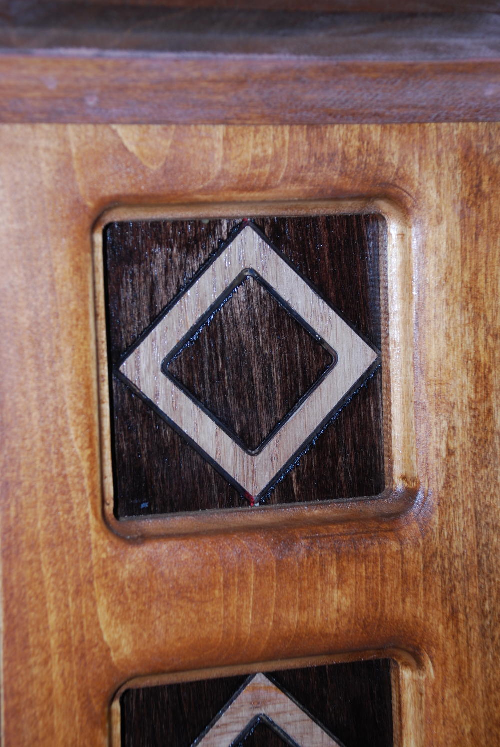 This example has a piece of clear acrylic inlay-ed into a birch board (the dark brown wood). A piece of Red Oak was then further inlay-ed into the acrylic (the light colored diamond). The result is a thin acrylic border around the oak which can be lit up by the LED strips which have been placed behind the acrylic. Check out our Image Gallery for further pictures of this project.