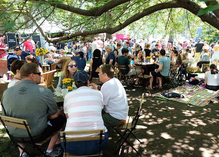 A large group relaxes in the 2018 Big Apple Barbecue's VIP section in the middle of Madison Square Park.
