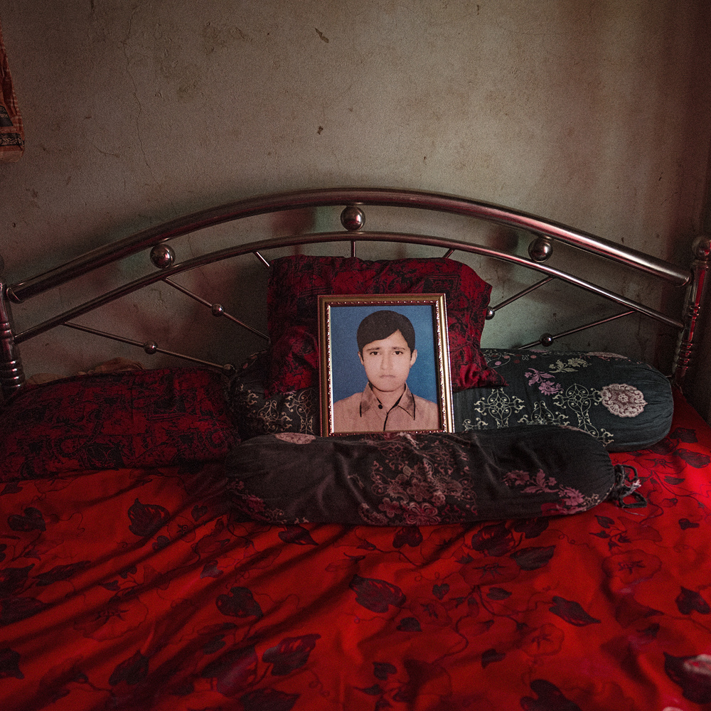 A portrait of Fazle Rabbi, son of Fajlul Haq Khan and Rahela Khanam, lies on the bed as the only living attestation of the 13-year old boy who died while buried under rubble in Rana Plaza