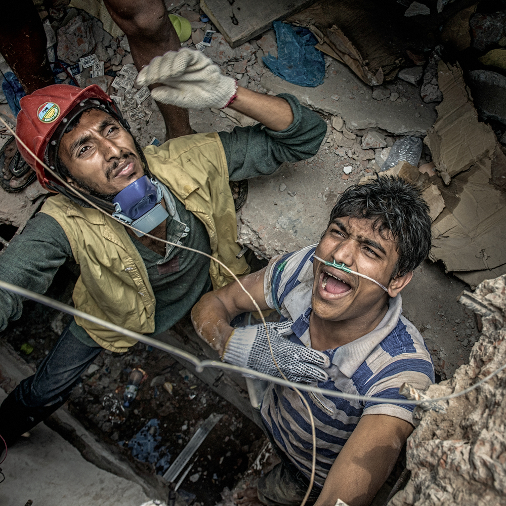 Mobarak Hossain, left, looks up while on a rescue mission to save victims stuck inside the collapsed structure