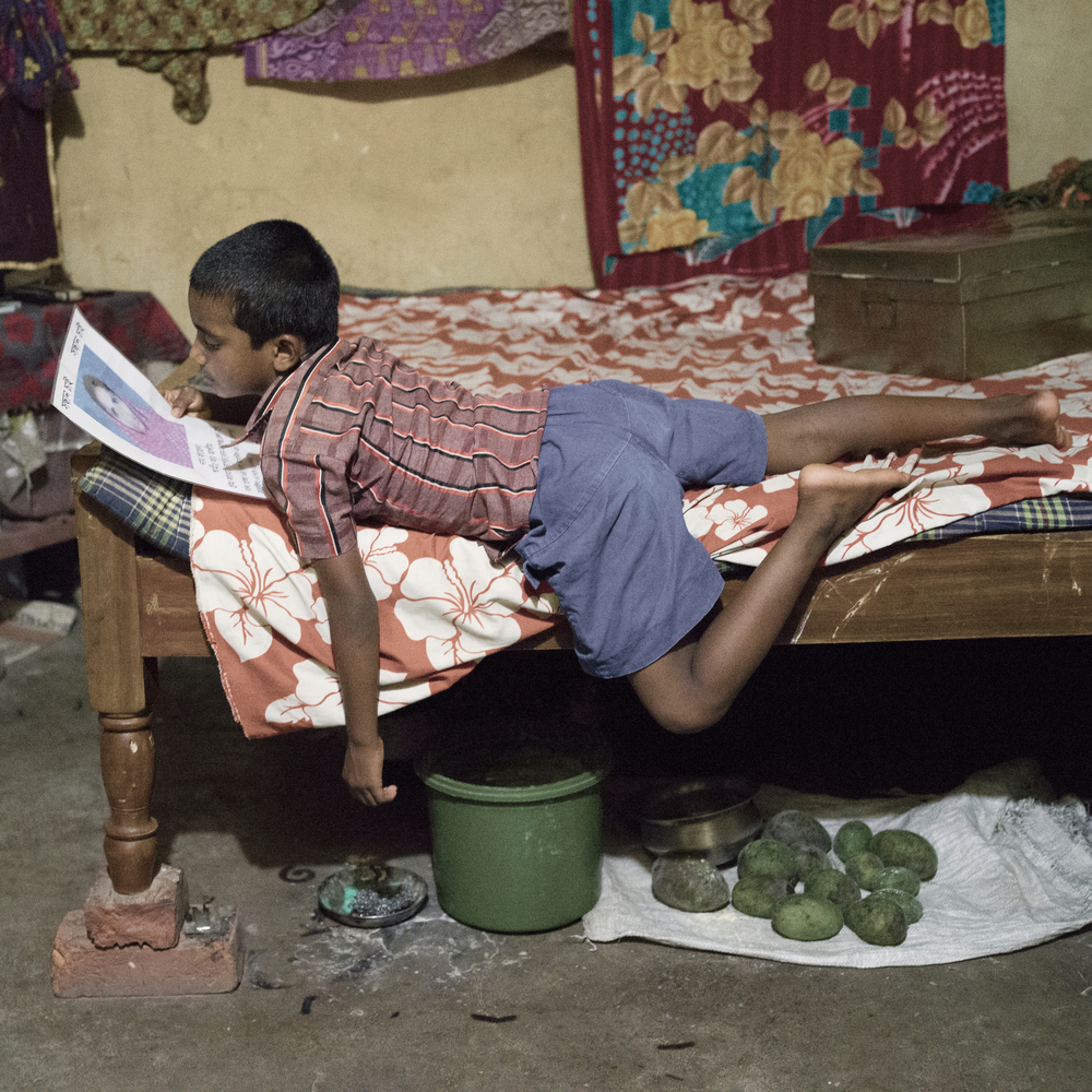 Kurban Hossain is watching his mother Jaheda Khatun's photo who breathed her last when Rana Plaza collapsed