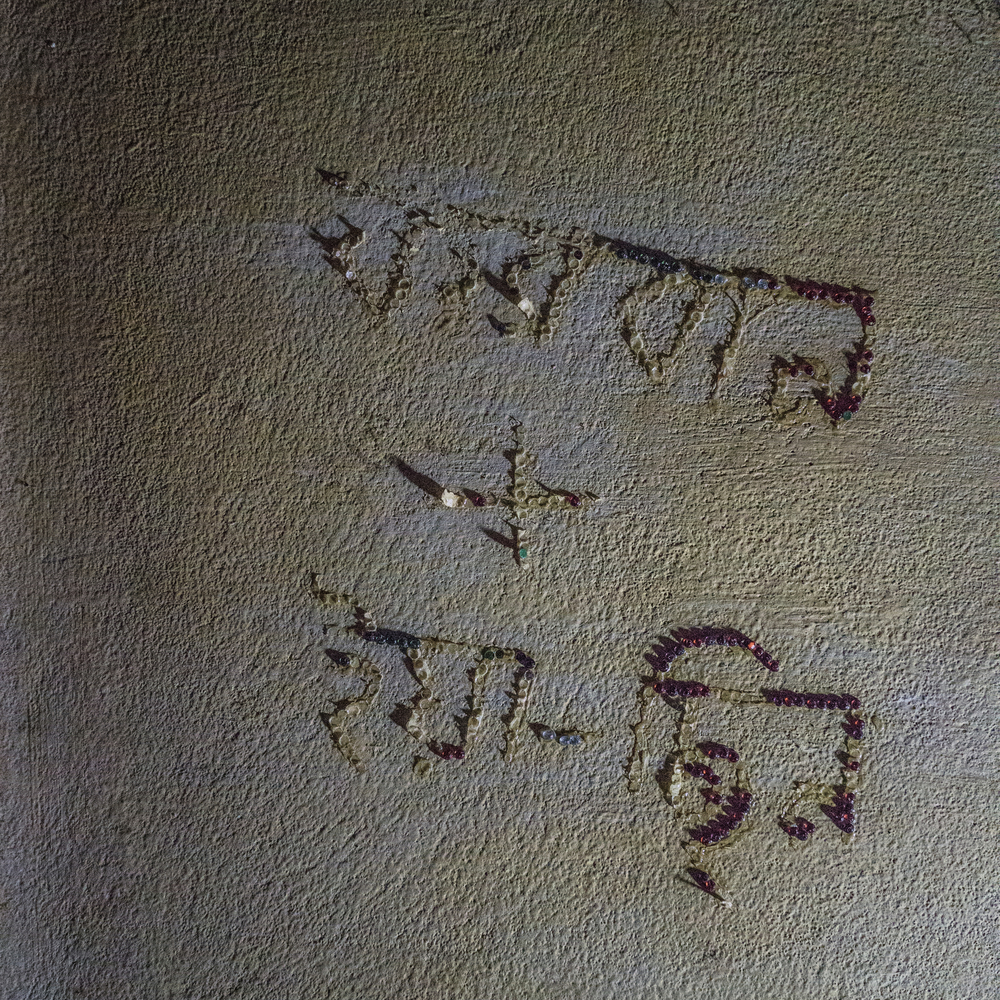 Jaheda and Alim's daughter writng her mother's reminiscence in letters on wall