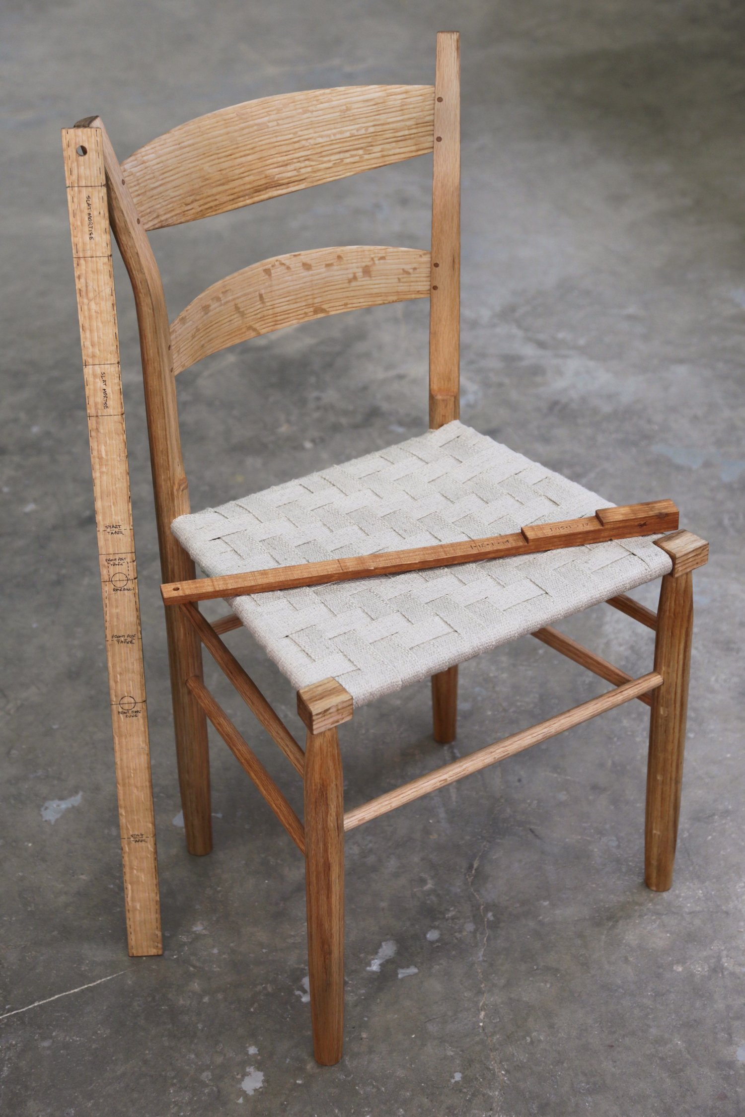 The chair is built in the greenwood ladder back style with rived parts shaped