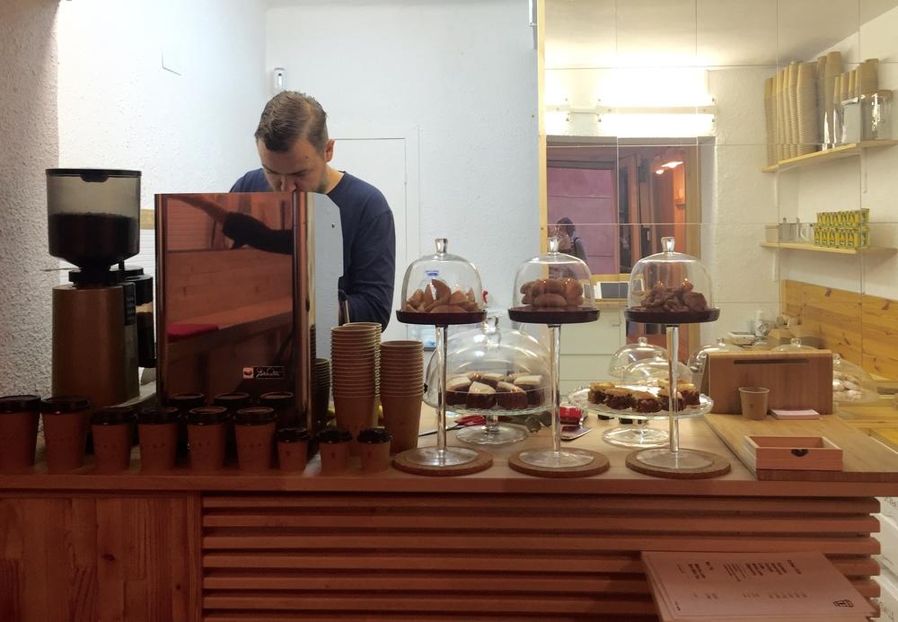 The barista at SYRA coffee preparing a coffee