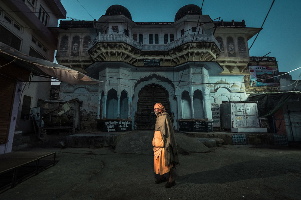 FUJIFILM X-T1 | XF10-24mmF4 R OIS @ 10 mm | 1/3 sec @ f/4 | ISO 800  There was no street light where I wanted to photograph the pilgrims going to do their morning bathing rituals in Pushkar lake. So I created my own street light with an orange gelled speedlight I hung off a canopy just outside of the frame.