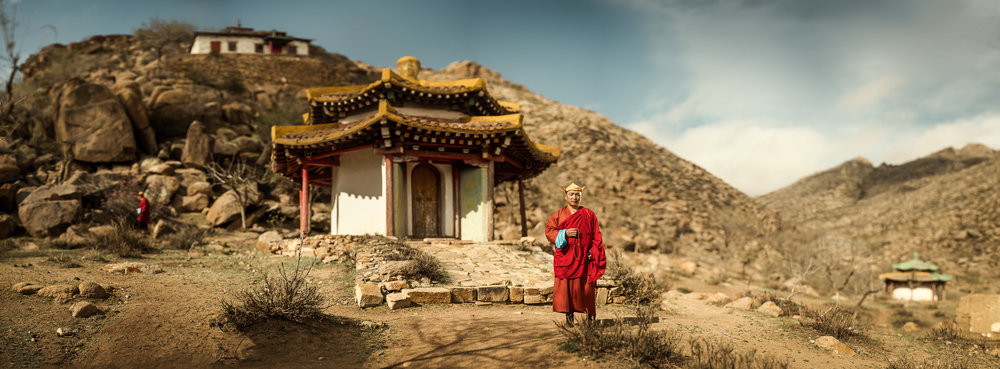 A monk posing in front of an ancient monastery.