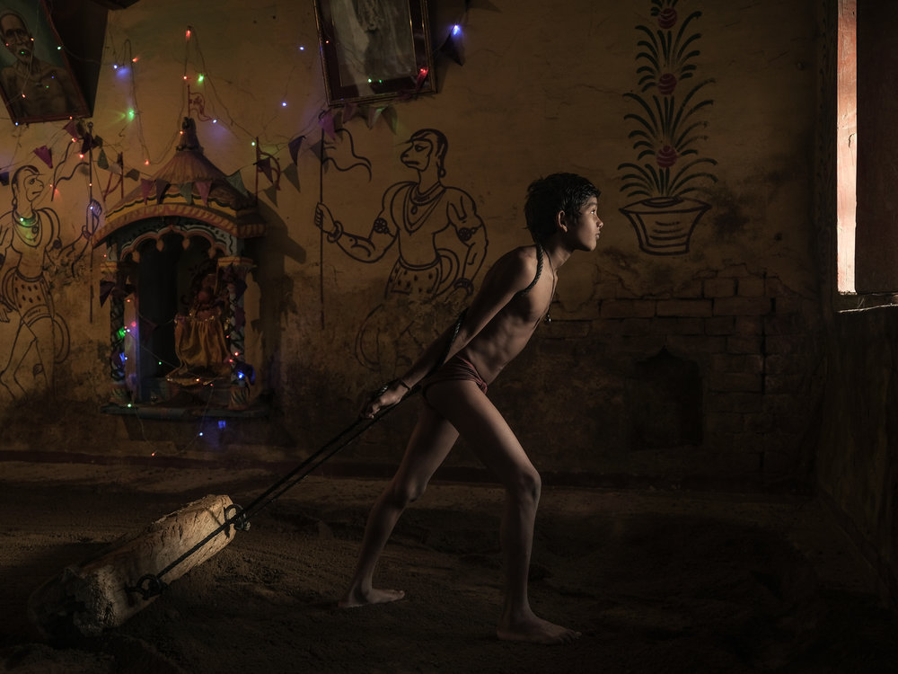 Boy straightening out the mud floor in a wrestling school in Varanasi.  Shot during my GFX Challenge video production.
