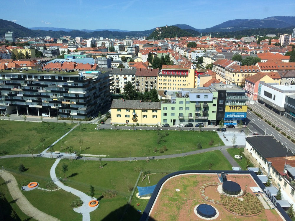 View toward the old town of Graz. Rising above the red roof tops is Schlossberg and in the foreground are 3 extensive green roofs.