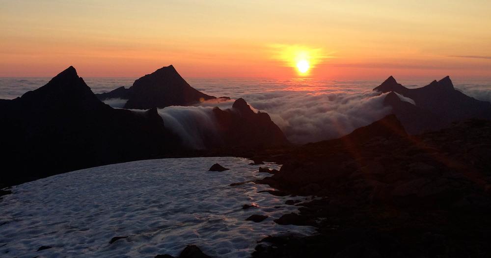 Midnatt og fortsatt sol ved fjellet Munken. Havskodda siger inn over fjellene.©Foto: Bjørnar Eidsmo