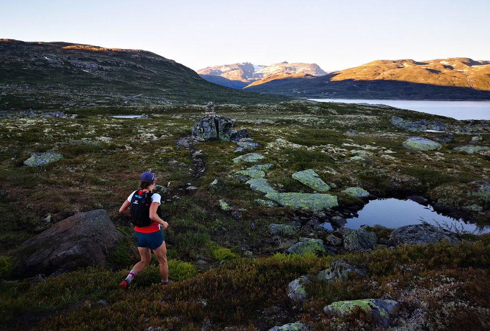 Det er like før sola går ned i Jotunheimen. Molly Bazilchuck er på vei til Tyin og CP2 på 60 km. Å løpe gjennom natten i fjellet er noe helt spesielt. Foto: Bjørnar Eidsmo.