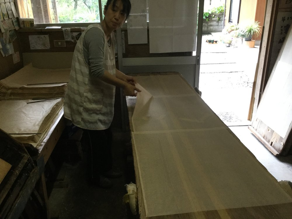 Removing sheets from drying board.