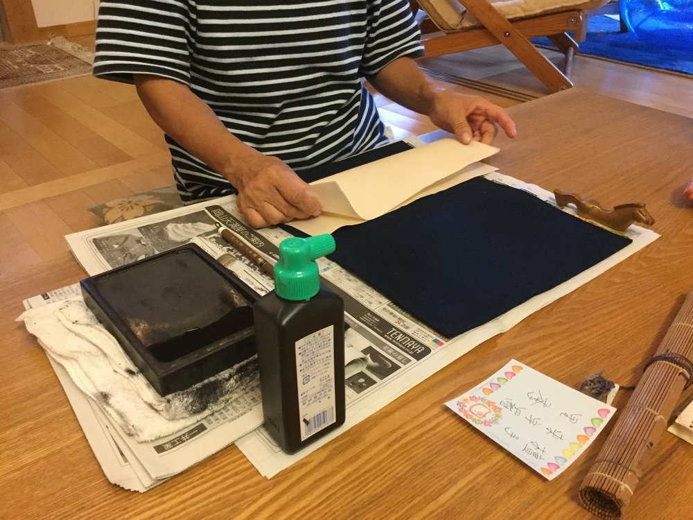 The shodo paper gets folded twice before starting. The creases help visualize the axis of the sheet for composition and balance. The newspaper protects the table, the black felt keeps the paper yielding to accept the brushstroke and the horse is a paperweight for the top of the sheet.