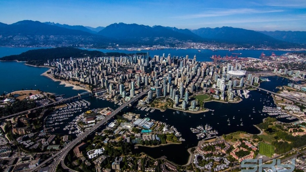 The area with the towers in the center is downtown. We live towards the right edge of the photo near the red cranes.  The dark area to the left of downtown is Stanley Park.