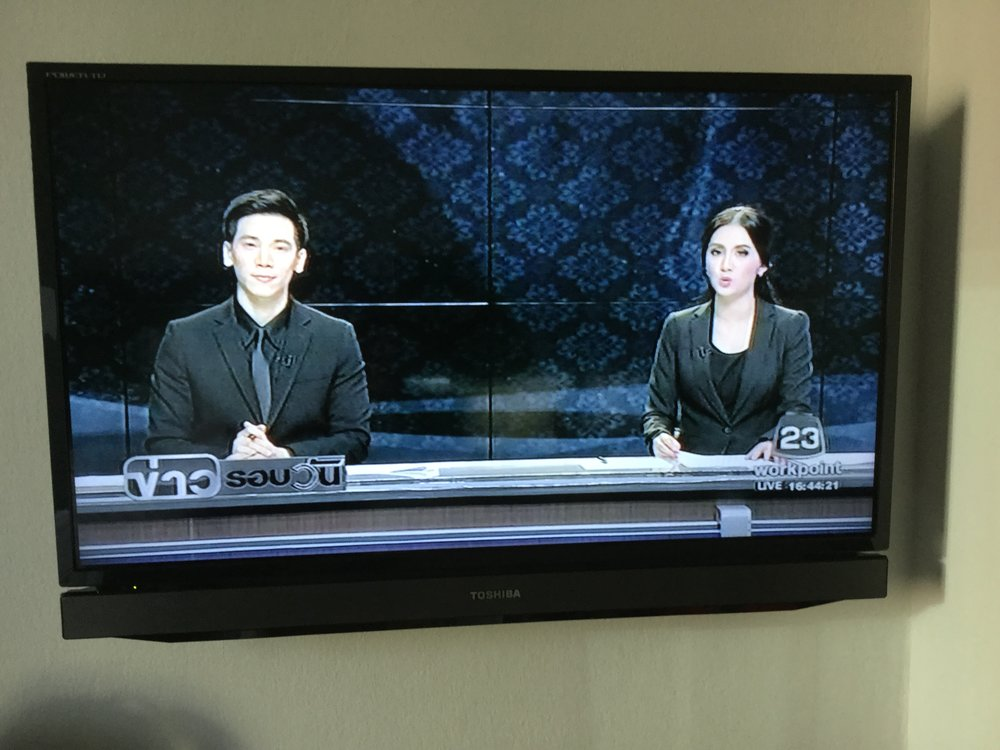 Television presenters are in all black, against a black background.