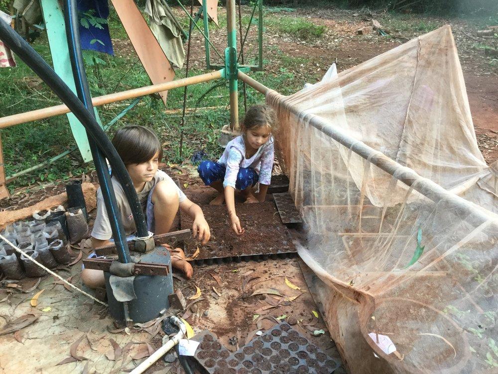 Lili and Zohar planting vegetables.
