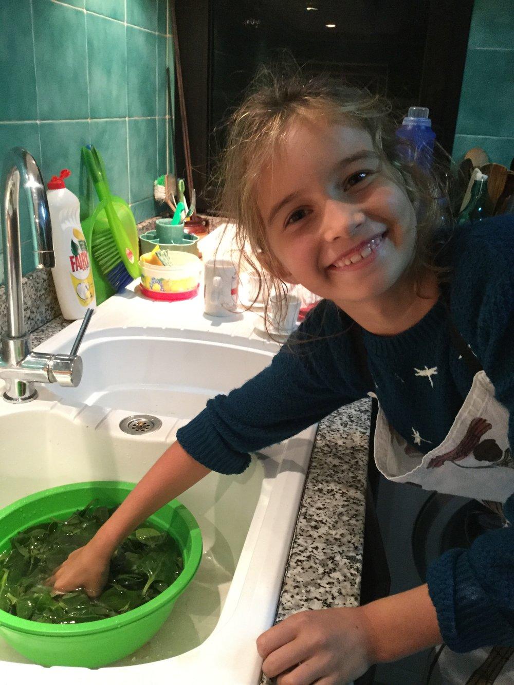Lili washing spinach.