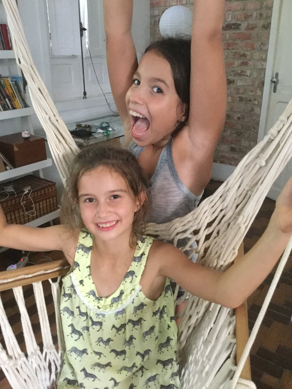 Isabela and Lili playing in our hanging chair.