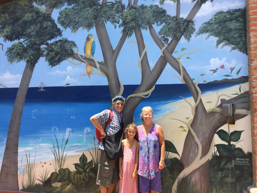 Family portrait in front of a mural at the square.