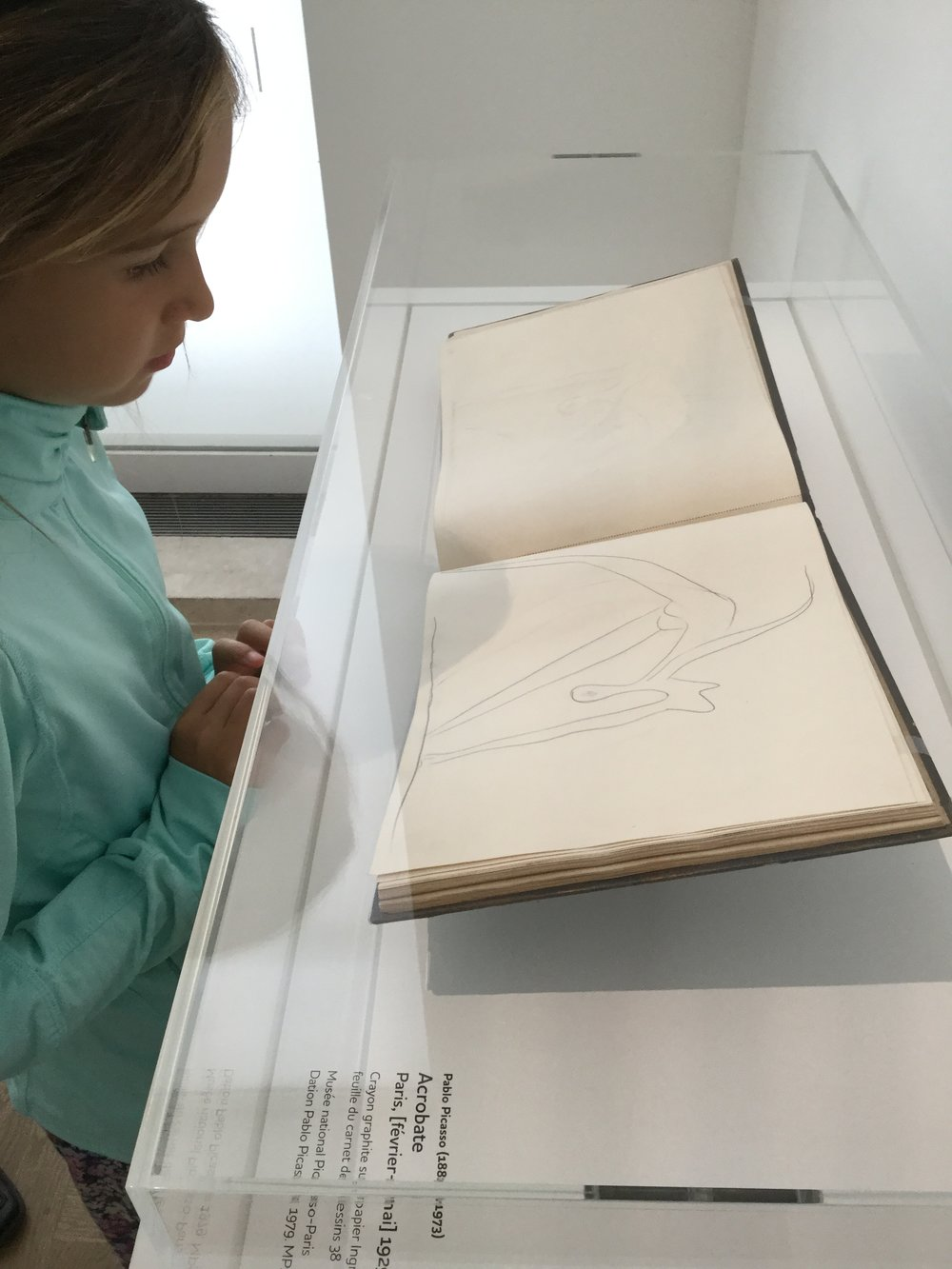 Lili looking at one of Picasso's notebooks. We said that she could also draw like that. And then we said that she could also do the pose the acrobat is in!