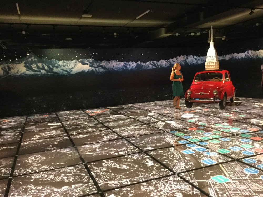 Amazing lit up floor of Torino with notes of car production history. The car is a Fiat Cinquecento from the 1950s.    Trivia question: Do you know what FIAT stands for?   Answer: Fabbrica Italiana Automobili Torino.