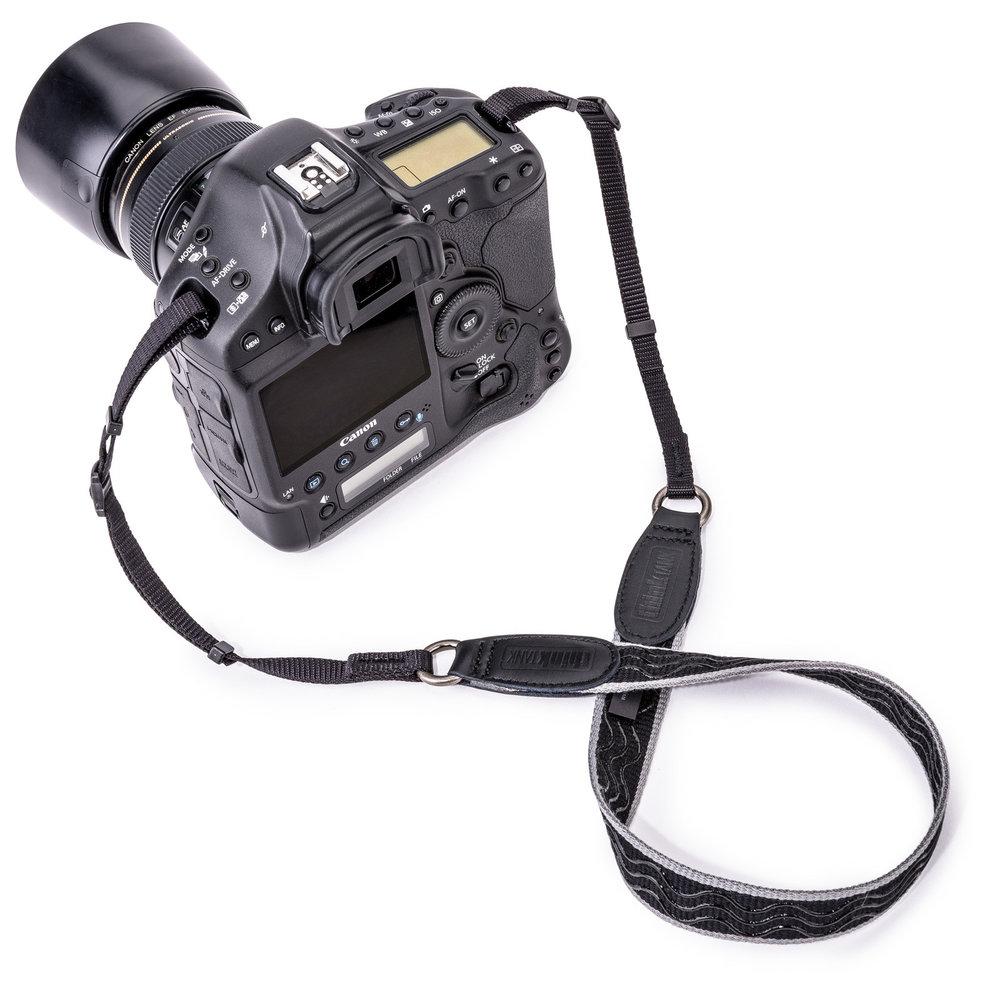 An obtrusive, narrow, non-slip camera strap - that's the goal
