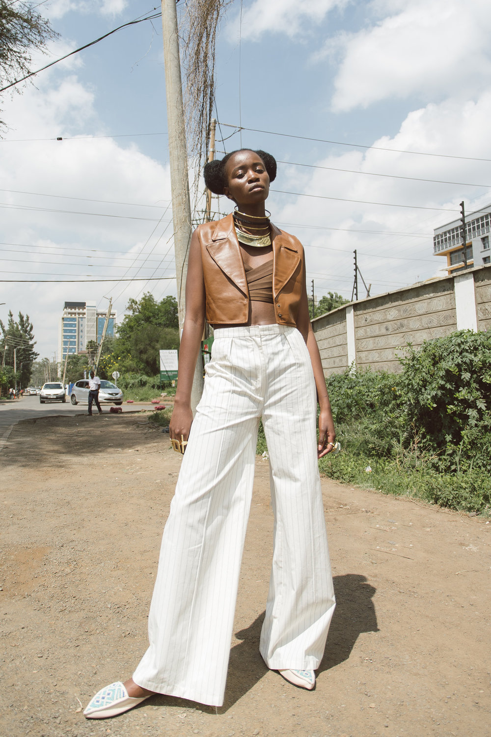 Anita wears M+K waistcoat, Lulu Mutuli bra top, Anyango Mpinga trousers, AdèleDejak choker and necklace and rings, Embody rings, Zinj Design slippers