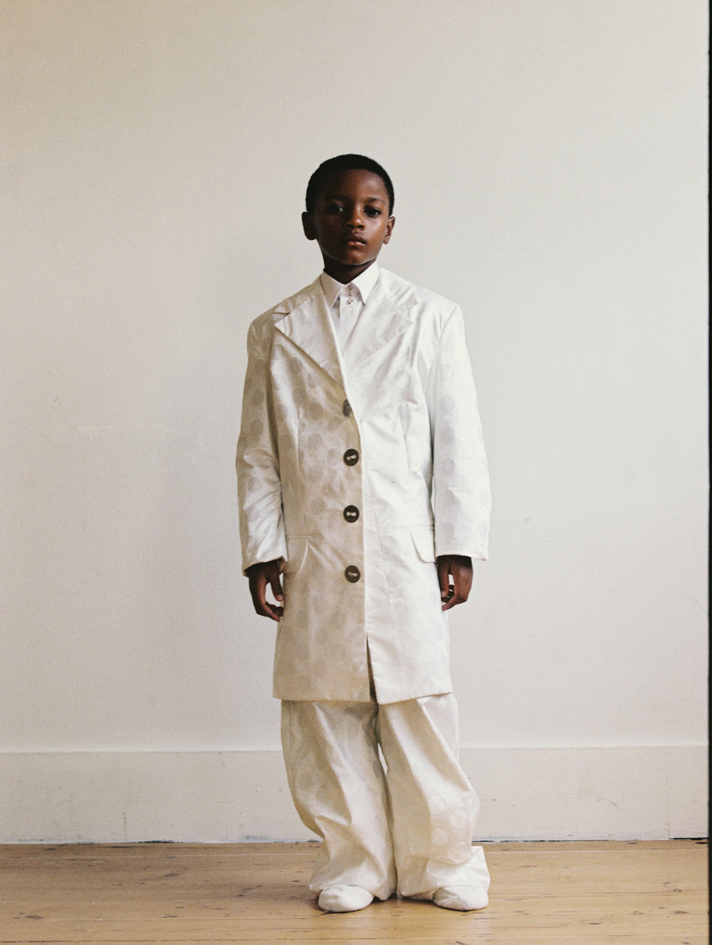 Isaiah wears Super Yaya jacket, stylist's own shirt, Slim Barrett earrings (worn on collar)
