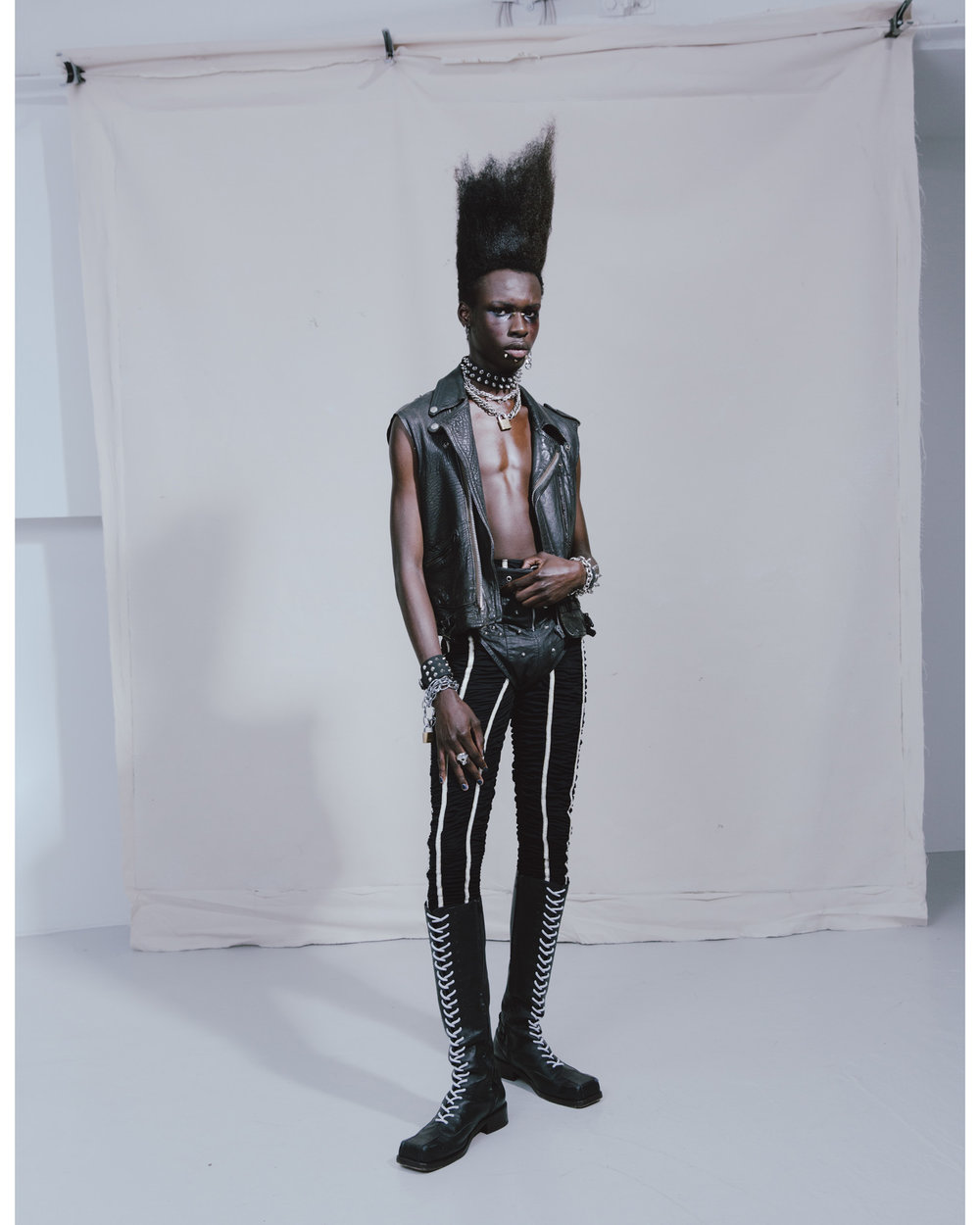 Emmanuel wears LEWIS LEATHERS ARCHIVE vest, RELLIK vintage briefs and belt, EDUN leggings, GIVENCHY hoop earring with cross, MOWALOLA chain earring, stylist's own choker, SLIM BARRETT chain necklace (with added safety pins), CONTEMPORARY WARDROBE padlock necklace, UNDERGROUND cuffs, NORTHSKULL ring, CHARLES JEFFREY LOVERBOY boots.