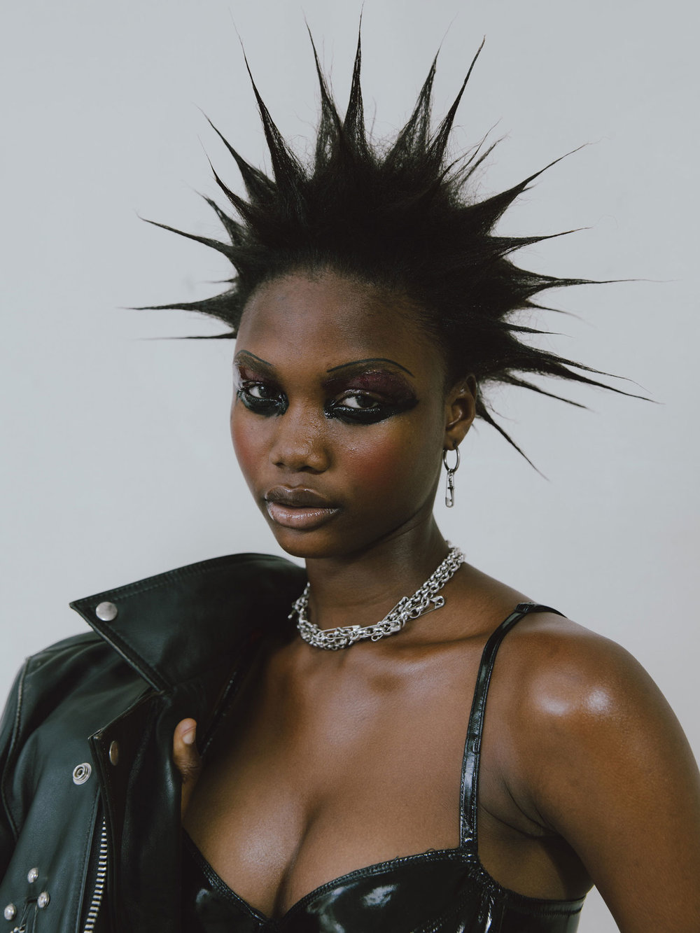 Olabisi wears LEWIS LEATHERS ARCHIVE jacket, DEBORAH MARQUIT bra, GIVENCHY earring (with added safety pin), SLIM BARRETT necklace (with added safety pins).