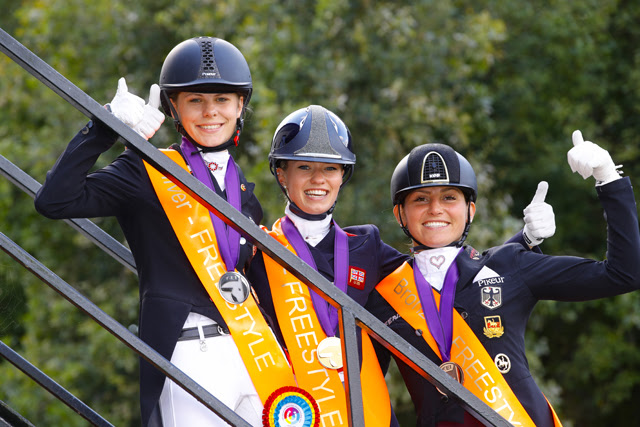It's a big thumbs up from Jil-Marielle Becks GER (silver), Charlotte Fry GBR (gold) and Lisa Maria Klossinger GER (bronze) after stepping off the Freestyle podium at the FEI European Dressage Championships U25 2018 in Exloo, The Netherlands today. FEI/Leanjo de Koster, DigiShots