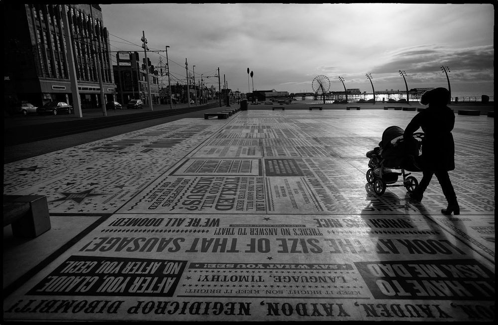 Blackpool lancashire golden mile sea front woman pram push chair art arty cold windy shaddow